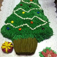 Christmas Tree buttercream using grass tip 233, tip 2 for garland, and fondant star. plain mm for lights. I used a tooth pic and made lines for the trunk...