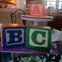 Toy Wooden Baby Blocks This cake was done with 6x6 blocks iced in Buttercream and airbrushed sides. The font plates were created with chocolate in icing bags on...
