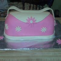 Pink Purse Cake  This is my 1st 3D cake. The cake is a devil's food chocolate cake with buttercream filling. Covered in pink MMF. The flowers are made...