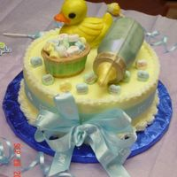 Baby Shower This cake is for a surprised baby shower for a friend at work. Yellow cake covered with buttercream. Rubber duckie, basket, and baby bottle...