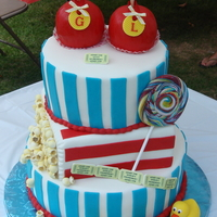 Carnival Cake 3 tiered fondant cake with handmade cake and fondant candy apples, personalized gum paste admission tickets, handmade fondant popcorn,...