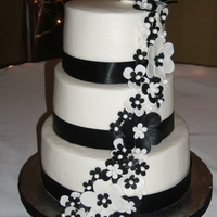 """megan"" 8/20/11 Bride just requested a black & white wedding cake. Ribbon at base of each tier. Hand made flowers. Buttercream."