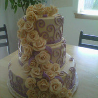 Ivory With Lavender Wedding Ivory buttercream frosted wedding cake with lavender scroll work, ivory gumpaste roses and lavender fondant ribbons.