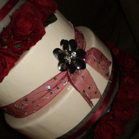 Rich Red And Black Wedding Cake (Dummy Cake For A Catering Service)) mmf covered wedding cake featuring sheer red and black ribbons, silver flower broaches, and silk roses