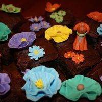 In A Field Of Spring Flowers Gumpaste flowers and gumpaste dog on top of chocolate cupcakes.