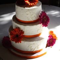 Orange And Fuschia Wedding Cake Buttercream frosting with a delicate scroll design.