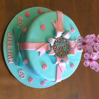 Exploding Cake  Blue & pink coloured pettinice covering chocolate mud cake. Icing made to look like an exploding present. Metallic cachous in centre of...