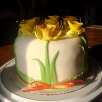 Spring Daffodil Cake White fondant covered daffodil cake with ribbon tied around the bottom.
