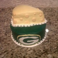 "Green Bay Packer Chessehead Cake All bc. ""chesse"" was a white cake with raspberry sauce on one layer, and vanilla mousse on the other. Green bay cake was 3 layers..."