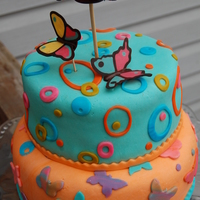 Butterflies Tier Cake In Teal And Orange Two tiers in fondant. Lower tier vanilla with strawberry jam. Top layer chocoate with marshmallow cream and skor bar pieces. The topper is...