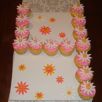 Daisy Cupcakes Vanilla flavored cupcakes with pink buttercream frosting and white fondant flowers with pink centers. Each cupcake has a yellow letter/...