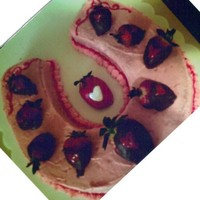 Strawberry Cake horseshoe coverd with choloate coverd strawberry on top of it