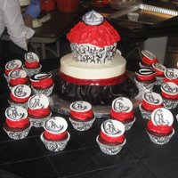 "Georgia University Cake 8"" cake with black fondant skirt and red band. Huge cupcake with the hand painted ""holder"" to mimic the 24 cupcakes that..."