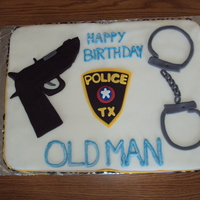 Police Officers Cake chocolate sheet cake on one side, vanilla on the other, both with vanilla BC. fondant was tinted/dyed at home. guns, badge, hand cuffs and...