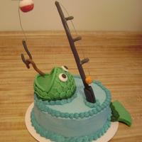 Fishin'  Fishing cake for my friend's husband. Buttercream icing, fondant fish, fishing pole, bobber, hook and worm. The fishing line is wire...