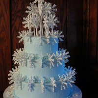 Snowflakes 3 tiers stacked, covered in light blue buttercream, sprinkled with clear glitter, with royal icing snowflakes