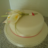 Single Tier Wedding Cake - Calla Lilies 10 inch round Madiera sponge, filled with buttercream and raspberry ja. Ivory sugarpaste (fondant) and petal paste (Gum) Calla Lilies, The...