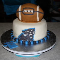 "Carolina Panther's Cake 2 layer 8"" topped with a 2 layer 6"" carved into the shape of a football."