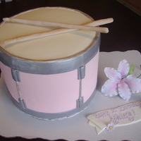 Pink Snare Drum Cake for 15 year old girl in band. Sticks & flower are out of gumpaste. It's a 4 layer 10inch round with supports in the middle.