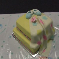 Baby Shower Yellow MMF with gumpaste baby booties and pacifier. Fondant baby blanket drapes down side.