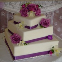 Jacake Top tier is real cake, bottom two are dummy cakes. Ribbon around edge and real flowers.
