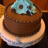 Pain Reliever  Chocolate cake, with teal gumpaste flowers. I have the dreaded buldge, but I didn't have time to let it settle. Our neighbor was...