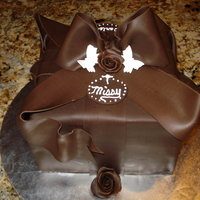 Pure Chocolate Gift Package With Bow Chocolate devils food cake with whipped chocolate and raspberry ganache filling. The outside is covered in modeling chocolate.