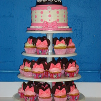 My First Minnie Mouse Cake And Cupcake Tower  This is my first time making a cupcake tower! 8 in buttercream minnie mouse cake with a half ball pan for minnie hat and fondant ears on...