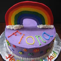 Rainbow Cake Rainbow dyed cake with purple chocolate buttercream and a fondant rainbow and flowers.