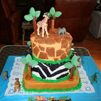 Safari Cake frosted in buttercream. No fondant here! Pretzels and gummy candies used for trees. Attached with sugar and Karo Syrup melting.