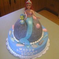 Ariel Cake yellow cake covered in homemade fondant. The dolls legs are wrapped in plastic wrap and in the cake. I made the tail out of fondant. I was...