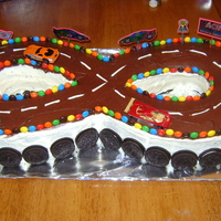 Race Car Cake I made this for my son's 7th birthday. I used 2 horse shoe pans then I cut another cake to fit the center. The kids loved it.