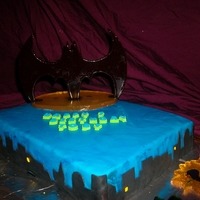 Batman Cake Batman symbol, biff and pow and the yellow oval all out of poured sugar. Everything else is fondant.