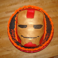 "Iron Man 12"" Iron man cake. The mask was made of rice crispy treats and covered in modeling chocolate. The flames are fondant."