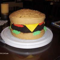 Hamburger Cake 3 layers, hamburger bun is yellow cake with buttercream, hamburger is chocolate with chocolate buttercream with Oreo cookie crumbs to make...