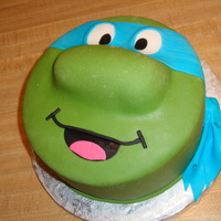 "Teenage Mutant Ninja Turtle 8"" round covered in MMF with decorations all in fondant. I used a Twinkie for the nose."