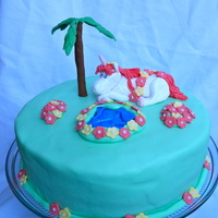 Hawaiian Unicorn The request was for a Hawaiian Unicorn cake. I added a palm tree, flowers draped on the unicorn, a pond, and flower patches. The birthday...