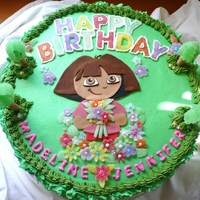 Dora The Explorer 1St Birthday Cake  This is a 4 layer cake with alternating vanilla and chocolate layers, chocolate pudding filling, buttercream icing, fondant character...