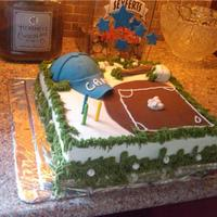 Baseball Cake   WASC, torted and filled w/ bc. Covered in BC. Chocolate fondant baseball diamond, gumpaste bat, cap, and baseballs. BC grass.