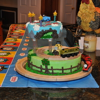 Thomas And Friends Two-Tier Birthday Cake I made this cake for my sons 4th Birthday. It had two wooden Thomas tracks placed on the cake with battery operated trains running on and...