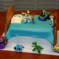 Toy Story Bithday Cake  Yellow and Chocolate cake with buttercream icing. Headboard is made of sugar cookie. Figures are toys. Blanket and pillow are made of...