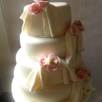 Four Tier Roses And Drapes Wedding Cake  Chocolate, lemon and vanilla tiers decorated in ivory icing. Each tier has a pearl border and small clusters of roses with a pearl spray...