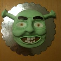 "Shrek  The nose, ""ears"", eye brows, etc are all sculpted from fondant. Entire cake covered in fondant.I carved out the shape of his face..."