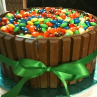 "Kit Kat Cake 8"" cake iced with chocolate frosting, kit kat bars around the sides, filled in with m&m's. This cake has endless possibilites..."