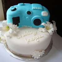 Candid Cake Nikon camera atop floral base of gum past lilies and daisies.