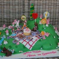 Fairy Picnic The cake is devil's food with chocolate ganache, covered in fondant. All details are made of fondant, except for the lollipops.