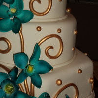 Wedding Teal And Gold Round cake with teal orchids with gold designs.