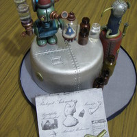 Steampunk Automata Cake This Steampunk cake is a fondant covered cake that was brush painted .Figures were made of cold porcelain and were brush painted too. Added...