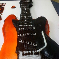 Electric Guitar Birthday Cake This is my first sculpted electric guitar cake. The head and neck were airbrushed in black. The body was airbrushed in red and orange. The...