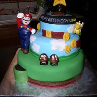 Mario Birthday White vanilla cake, strawberry preserves filling, vanilla buttercream.Covered in fondant, layered & textured to mimic the Super Mario...
